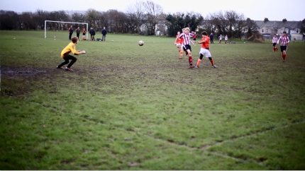 Isaac (in orange) scores a fine goal from just around the penalty spot